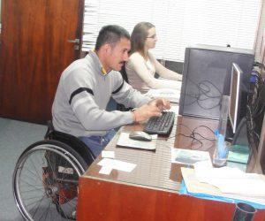 Imagen ilustrativa de personas con y sin discapacidad trabajando con una computadora en una oficina.