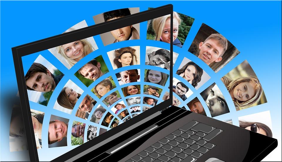 imagen ilustrativa Se observan retratos de varias personas dispuestas en forma semicircular, y en primer plano una notebook sin pantalla que permite ver la imagen de fondo.